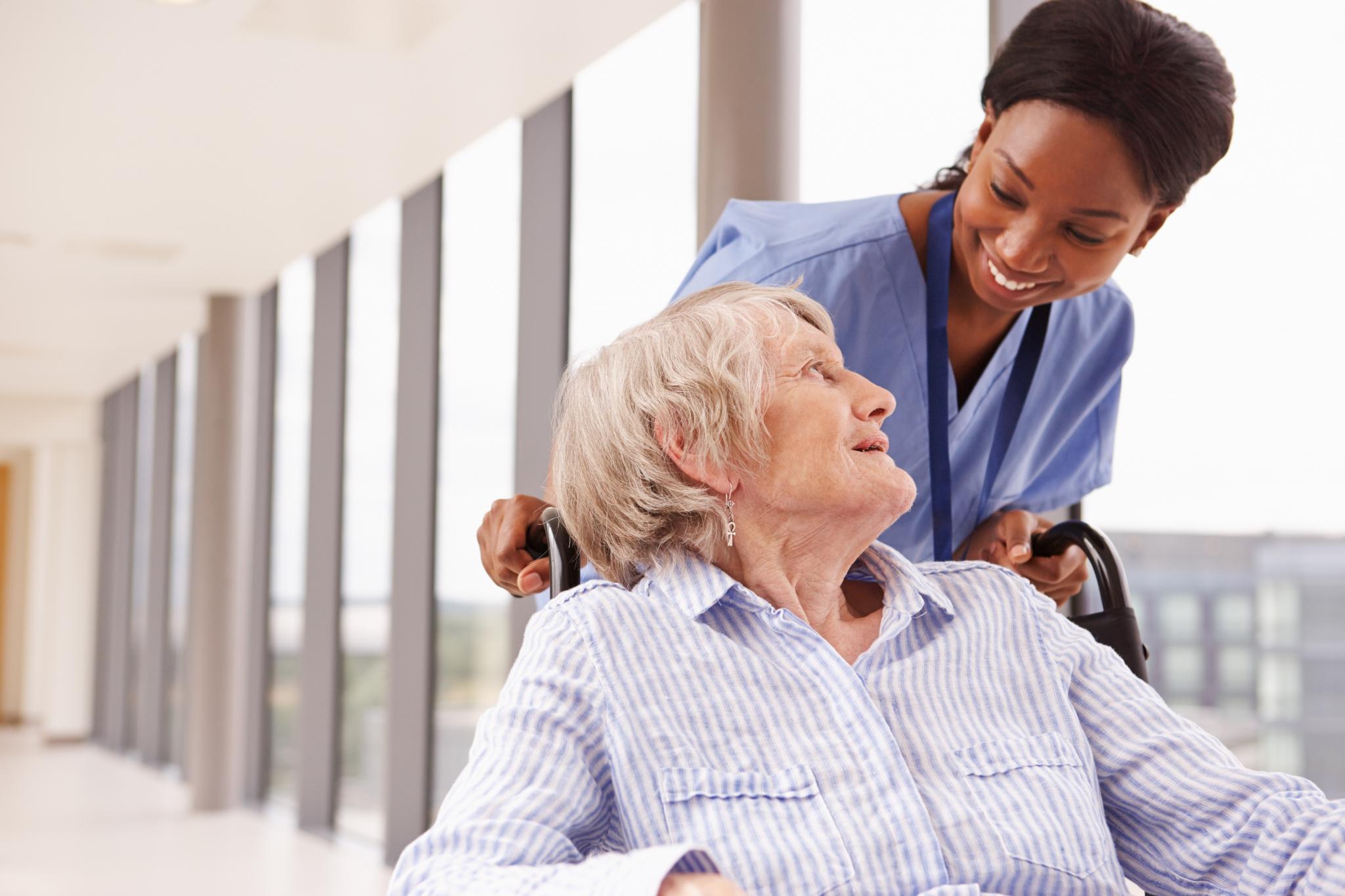Nurse Pushing Senior Patient In Wheelchair Along Corridor